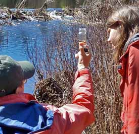 Photo of Macouners examining a swamp-water sample