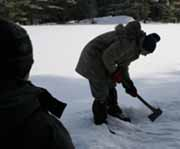 Photo of Rob chopping hole in ice