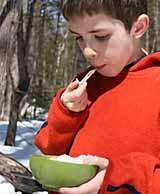Photo of Francis Caron tasting maple taffy