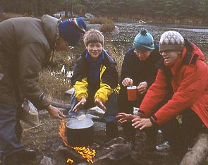 Photo of Rob cooking breakfast for Andy Wagner, William Godsoe, and Hugo Kitching
