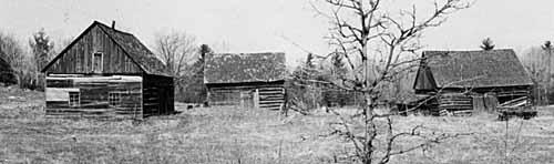 Photo of abandoned log buildings at Pakenham in 1970