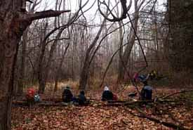 Photo of Macoun Club members eating lunch in the woods