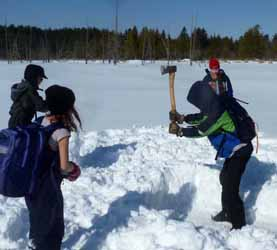 Photo of boy chopping hole in pond ice