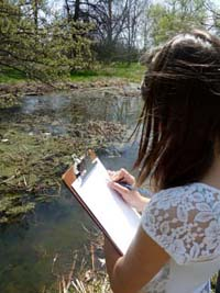 Photo of girl drawing toads by pond
