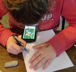Photo of girl sketching frog from her smart-phone screen