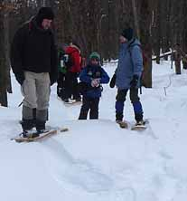 Photo of group on snowshoes coming through the woods