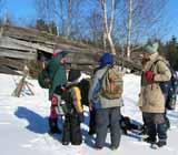 Photo of Macoun group at broken-down log cabin