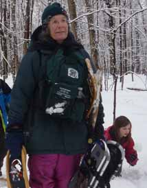 Photo of Diane Kitching laden with kids' snowshoes
