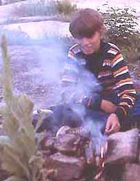 Photo of Macoun Club member Lorin Gaertner tending a campfire