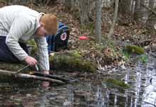 Macoun Club president Gabriel Levac sampling pond water